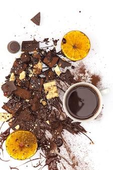 Het bovenaanzicht van stapel gebroken chocolade en warme chocolademelk op witte tafel in studio