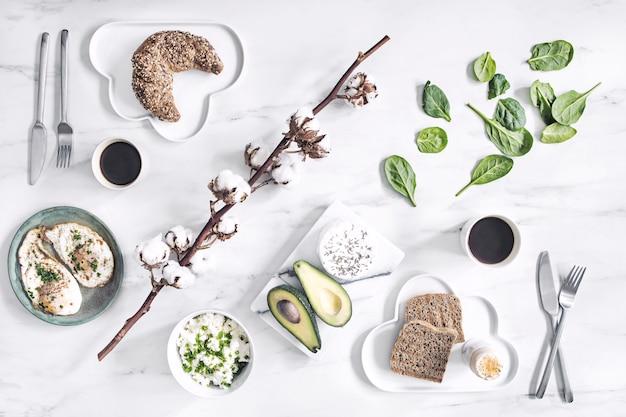 Het bovenaanzicht van superfood op de witmarmeren tafel. plat leggen. variuos groenten ingrediënten en gezonde voeding voor vegetariërs. ontbijttafel.