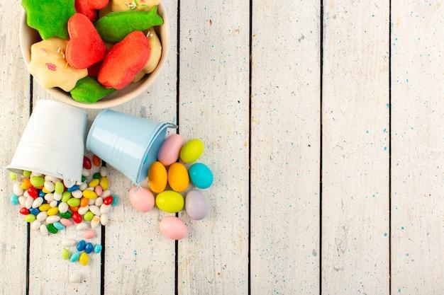 Het bovenaanzicht van verschillende kleurrijke koekjes vormde veelkleurige veelkleurige binnenplaat met suikergoed op het grijze oppervlak