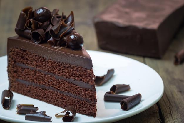 Het bovenste laagje van de chocoladecake met chocoladekrul op houten achtergrond