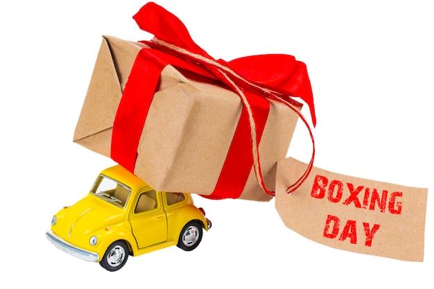 Het boxing day-concept. gele retro speelgoedauto leveren van geschenken doos met tag met tekst boksendag op witte achtergrond.