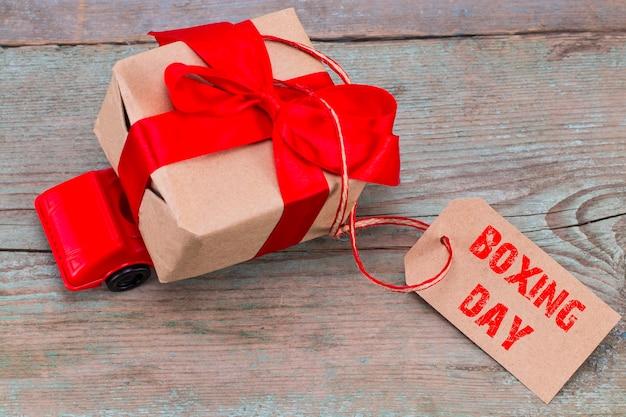 Het boxing day-concept. rode speelgoedauto die een geschenkdoos levert met een tag met de tekst: boxing day op houten ondergrond.