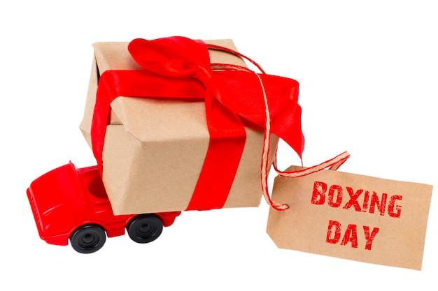 Het boxing day-concept. rode speelgoedauto leveren van geschenken doos met tag met tekst: boxing day op witte achtergrond.