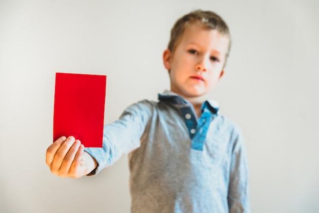 Het boze gezichtskind die een rode kaart als waarschuwing tonen, houdt intimiderend concept, lege achtergrond tegen.