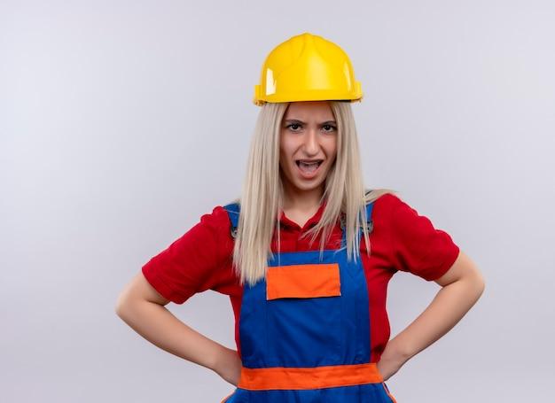 Het boze jonge meisje van de blonde ingenieursbouwer in eenvormige en tandsteunen met handen op taille op geïsoleerde witte ruimte
