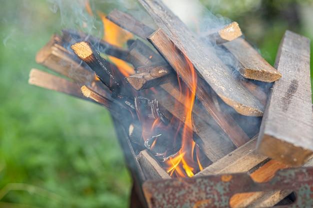 Het brandhout in de grill brandt met een fel oranje vuurvlam op een natuurlijke groene achtergrond. voorbereiding voor het koken van vlees op de grill in de natuur. vuur vlammen en rook