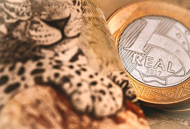 Het braziliaanse echte bankbiljet van vijftig reais en een echte munt in close-up foto