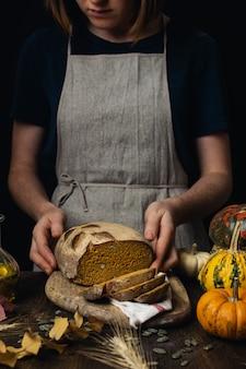 Het broodbrood van de zuurdesem organisch pompoen, vrouwelijke handen op donkere houten lijst