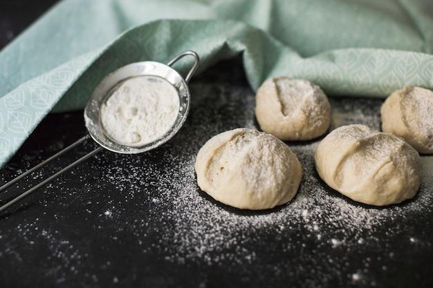Het brooddeeg van broodjes het klaar om met bloem op zwarte achtergrond te bakken