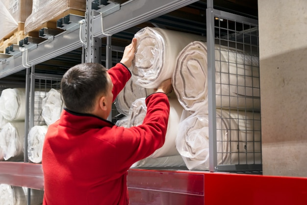Het broodje van de mensenlading van matras in pakhuis