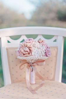 Het bruids boeket van roze kunstbloemen ligt op een roze elegante uitstekende stoel op een vage tuinachtergrond, selectieve nadruk