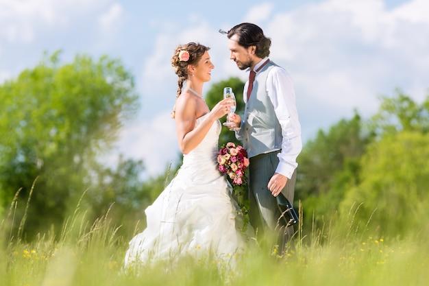 Het bruids paar viert huwelijksdag met champagne