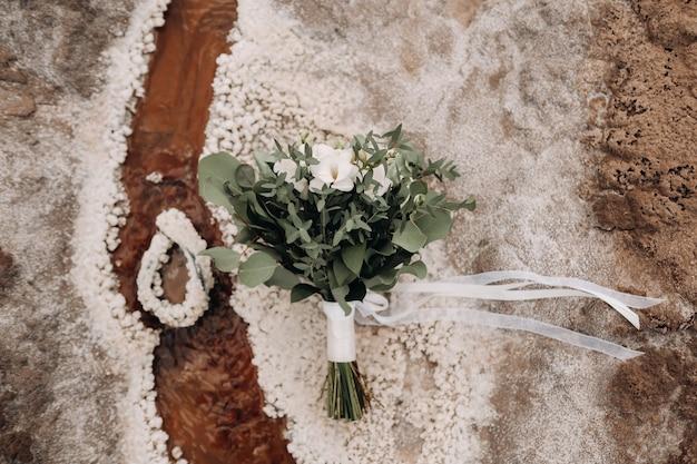 Het bruidsboeket rust op een zoute textuur.het decor op de bruiloft.