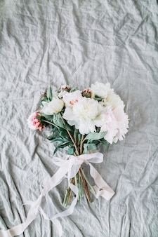 Het bruidsboeket van huwelijksbloemen met witte pioenen met lint op grijs linnen