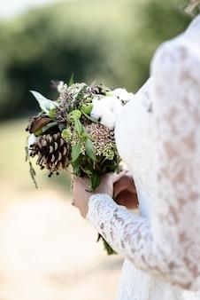 Het bruidsboeket van kegels en katoen close-up in de handen van de bosachtergrond van de bruidkantenjurk Premium Foto