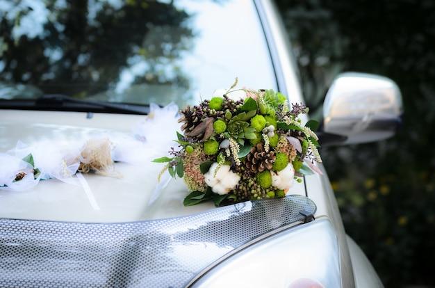 Het bruidsboeket van kegels en katoen op de motorkap van de trouwauto