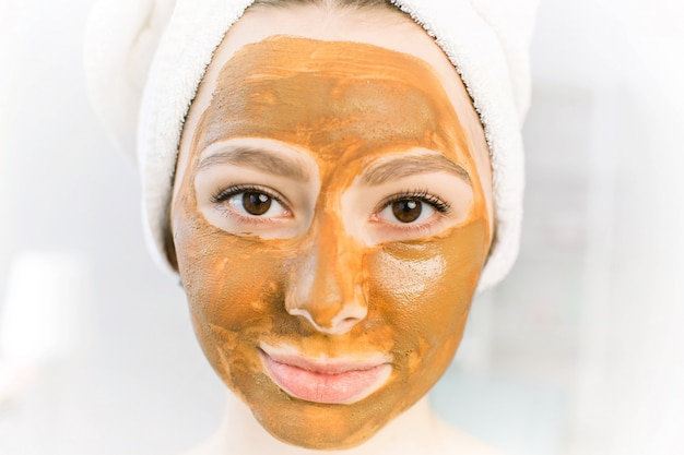 Het bruine masker van schoonheidsmiddelen van klei op het mooie jonge vrouwelijke gezicht, dat op wit wordt geïsoleerd