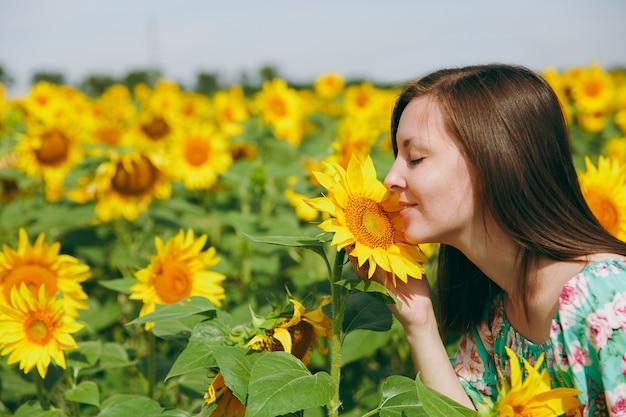 Het brunette meisje snuffelt aan een zonnebloem in het veld