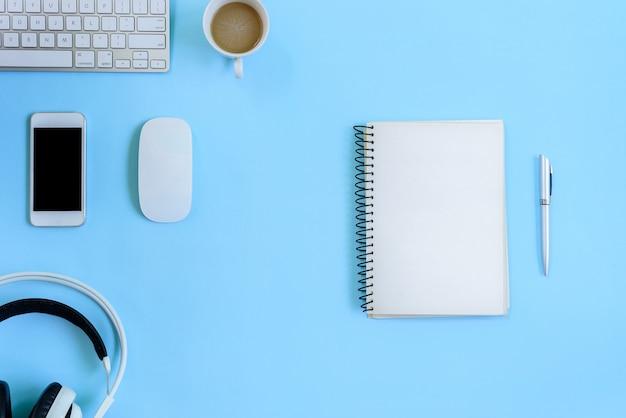 Het bureau blauwe bureau en apparatuur voor het werken in bovenaanzicht en plat op blauwe achtergrond