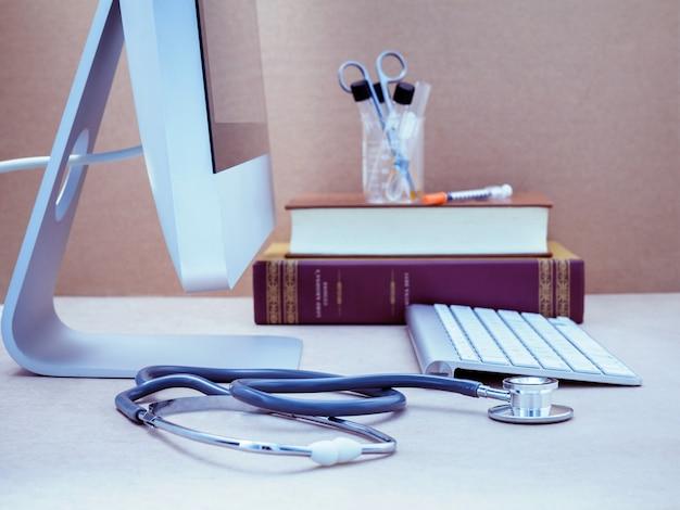 Het bureau van de arts met computer en medisch handboek met ondiepe diepte van gebied.