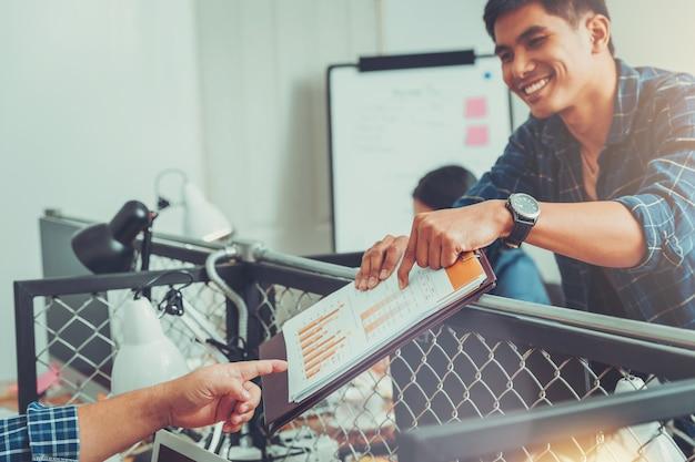 Het bureauzakenman van het geluk verhelderend resultaat van zaken met collega, die strategie gelukkige bespreking verklaart