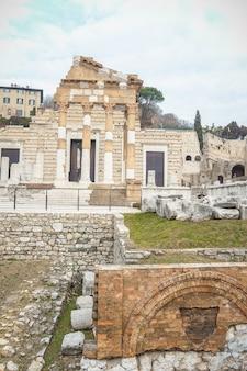 Het capitolium of de tempel van de capitolijnse triade in brescia was de belangrijkste tempel in het centrum van de romeinse stad brixia. het wordt momenteel vertegenwoordigd door fragmentarische ruïnes met een romeins amfitheater
