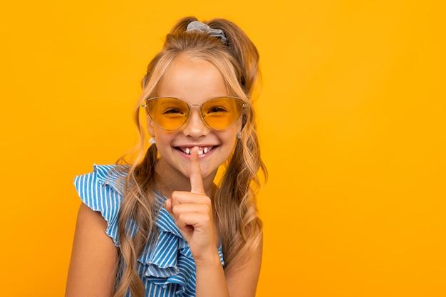 Het charmante blonde meisje in een kleding en zonnebril vraagt om rustiger te zijn, houdt een vinger bij haar mond op geel met exemplaarruimte