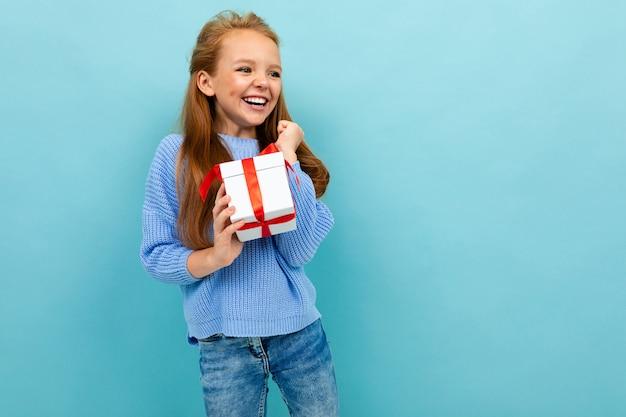 Het charmante gelukkige europese meisje met een gift ontving voor valentijnskaartendag op een lichtblauwe achtergrond