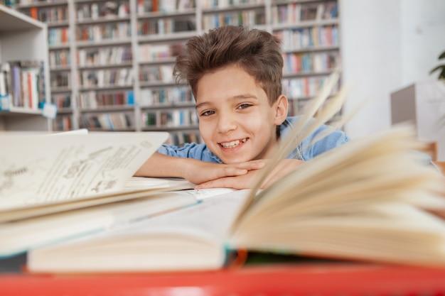 Het charmante jonge jongen glimlachen die bij de bibliotheek na het lezen en het bestuderen rusten