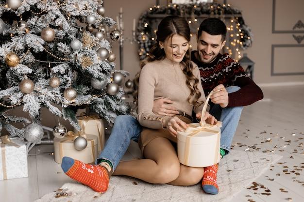 Het charmante jonge paar in comfortabele huiskleren opent huidige vakjes vóór een kerstboom