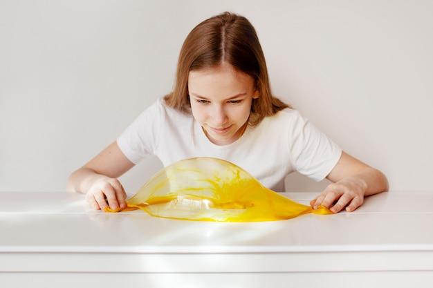 Het charmante meisje glimlacht en maakt een bel van geel slijm