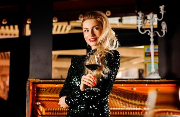 Het charmante meisje in een avondjurk geniet van muziek en drinkt rode wijn