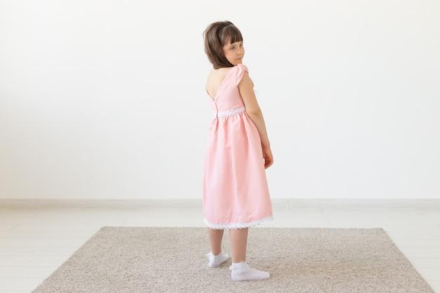 Het charmante meisje in een roze jurk glimlacht en kijkt in de camera tegen het oppervlak van een witte muur