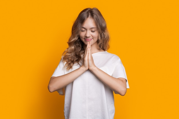 Het charmante meisje in vrijetijdskleding bidt op een gele studiomuur die met palmen gebaart en met gesloten ogen glimlacht