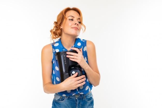Het charmante meisje koestert een koffiezetapparaat op wit