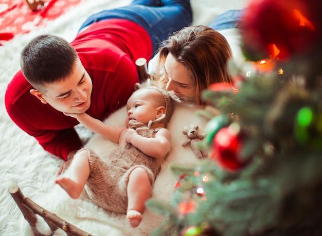 Het charmante meisje ligt op zacht beige hoofdkussen onder een kerstboom terwijl de moeder en de vader met haar spelen