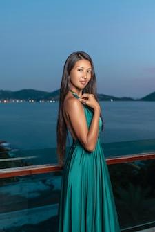 Het charmante mooie gemengde rasmeisje stellen die zich op het terras bevinden