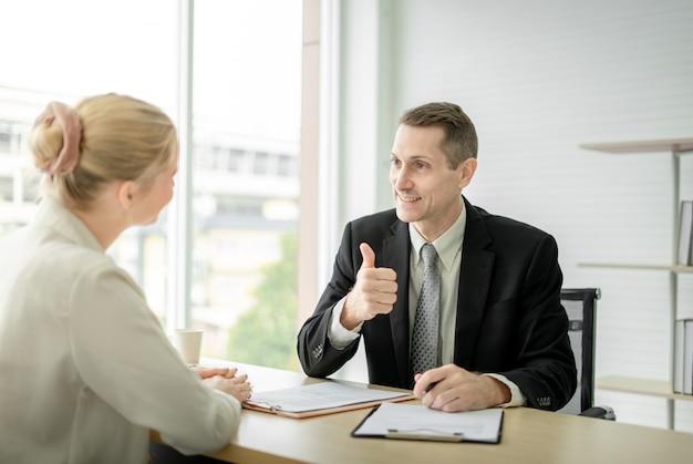 Het chef- zakenman doen beduimelt omhoog gelukwens aan vrouwenwerknemer bij bureau in bureauruimte