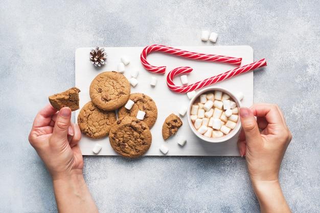 Het chocoladeschilferkoekje, kerstrietkaramel cup cacao en marshmallowkegels decoraties op een grijs. copyspace frame.