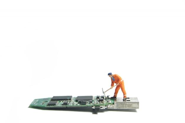 Het cijfer dat van de technicusarbeider zich op een oude usbflitsaandrijving bevindt. it-ondersteuningsconcept.