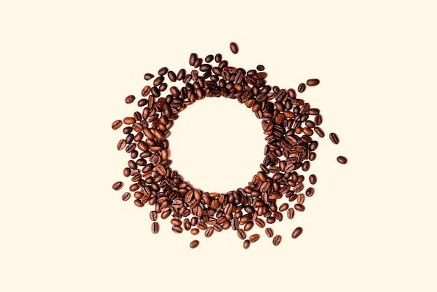 Het cirkelkader van geroosterde bruine die koffiebonen op witte achtergrond worden geïsoleerd kan als achtergrond of textuur gebruiken.