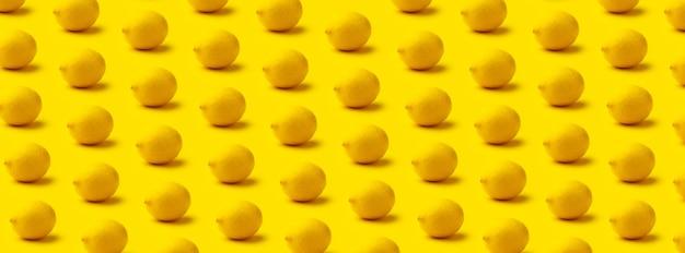 Het citroenpatroon op een gele achtergrond met een schaduw, panoramisch beeld