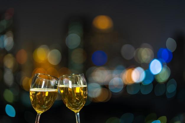 Het clinking met twee biermok of glazen over de foto vaag van cityscape voor viert