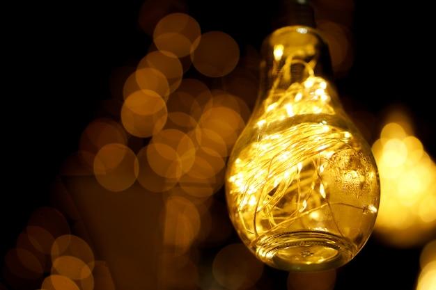 Het close-up decoratieve leidene licht in uitstekende gloeilamp met schakelt lichten in nacht gloeiend en onscherp in.