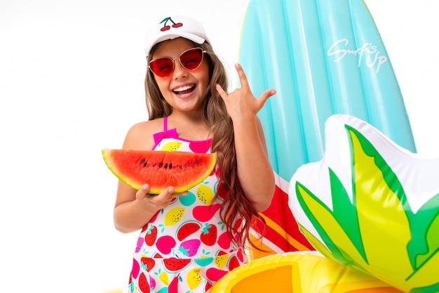 Het close-up glimlachende meisje op een witte achtergrond, het kind houdt in zijn handen een watermeloen omringd door zwemmende toebehoren