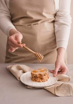Het close-up overhandigt gietende honing op brood