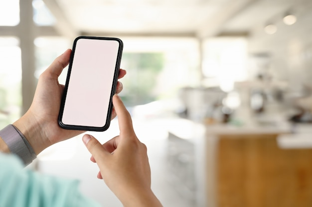 Het close-up schoot mannelijke handen gebruikend mobiele telefoon in koffie.