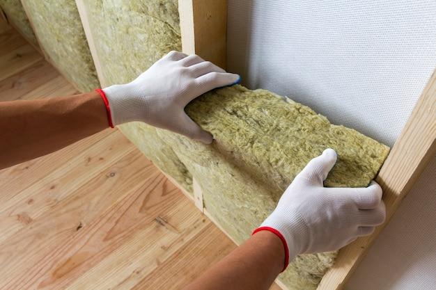 Het close-up van arbeider dient witte handschoenen in isolerend personeel van de rotswolisolatie in houten kader