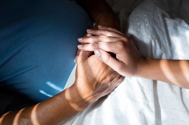Het close-up van artsen overhandigt het troosten van hogere patiënt in slaapkamer