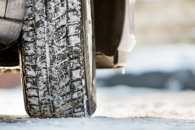 Het close-up van auto rijdt rubberband in diepe sneeuw. transport- en veiligheidsconcept.